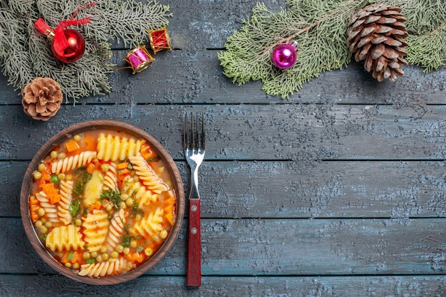 Vue de dessus délicieuse soupe de pâtes à partir de pâtes italiennes en spirale avec des verts sur le bureau bleu foncé cuisine soupe de pâtes plat de couleur dîner