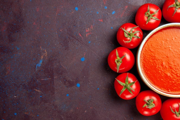 Vue De Dessus Une Délicieuse Soupe De Tomate Entourée De Tomates Rouges Fraîches Sur Fond Sombre Soupe De Tomate Sauce Plat De Repas Photo gratuit