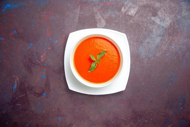Vue de dessus délicieuse soupe de tomate plat savoureux avec une seule feuille à l'intérieur de la plaque sur un fond sombre sauce plat couleur tomate soupe de dîner