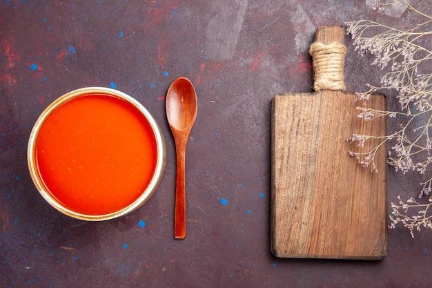 Vue de dessus délicieuse soupe de tomates cuite à partir de tomates fraîches sur un plat de bureau sombre sauce repas soupe de tomates