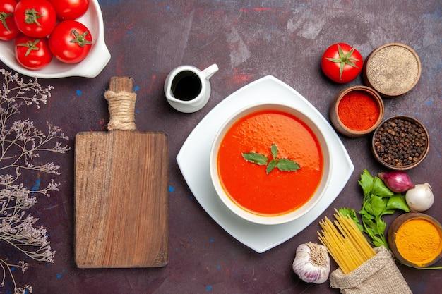 Vue de dessus une délicieuse soupe de tomates avec des tomates fraîches et des assaisonnements sur le plat de fond sombre sauce repas couleur tomate