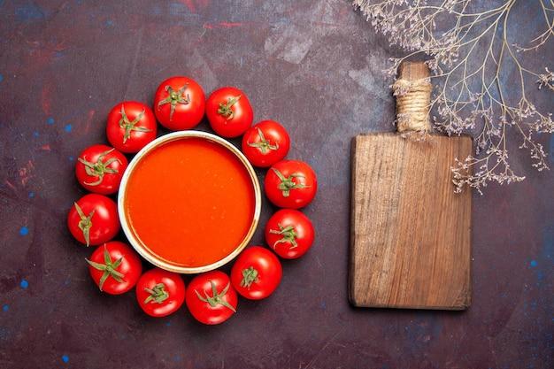 Vue de dessus délicieuse soupe de tomates avec des tomates rouges fraîches sur le plat de dîner de repas de soupe de tomate de fond sombre
