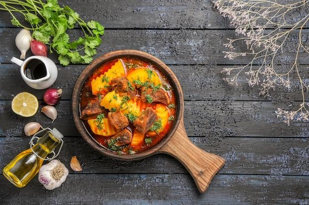 Vue de dessus délicieuse soupe de viande avec pommes de terre et légumes verts sur le bureau sombre