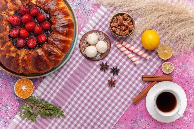 Vue de dessus délicieuse tarte aux fraises à la cannelle et tasse de thé sur rose
