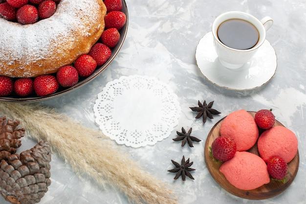 Vue de dessus délicieuse tarte aux fraises avec du thé sur blanc clair
