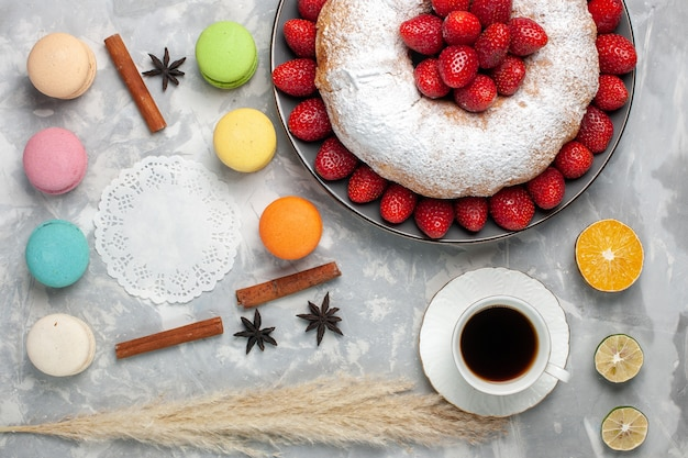 Vue de dessus délicieuse tarte aux fraises avec du thé et des macarons sur blanc