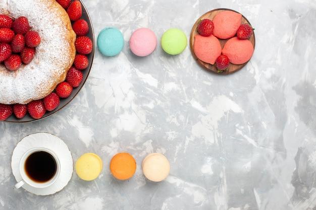 Vue de dessus délicieuse tarte aux fraises avec du thé et des macarons sur la lumière