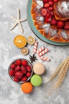 Vue de dessus délicieuse tarte aux fraises avec macarons sur surface légère cuire au four biscuit gâteau sucre tarte sucrée cookie