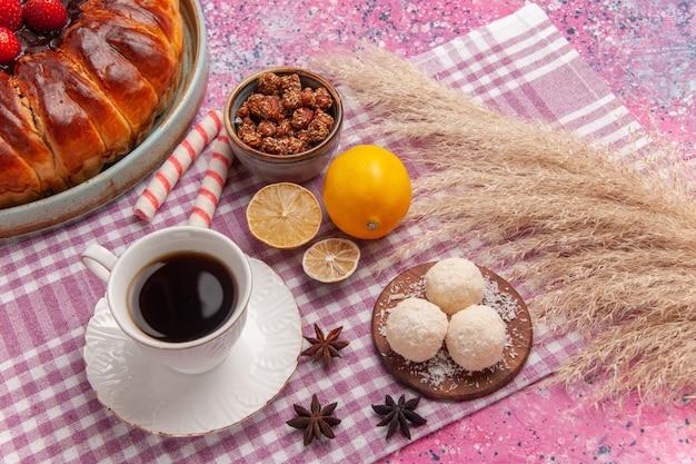 Vue de dessus délicieuse tarte aux fraises avec une tasse de thé sur le rose clair