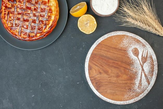 Vue de dessus délicieuse tarte aux fruits avec confiture sur pâte à gâteau grise biscuit tarte au sucre thé au four sucré