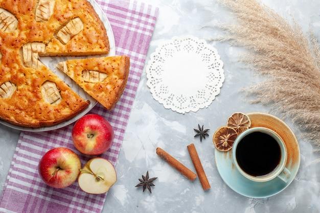 Vue de dessus délicieuse tarte aux pommes à l'intérieur de la plaque avec des pommes et tasse de thé sur le fond clair gâteau biscuit tarte sucré