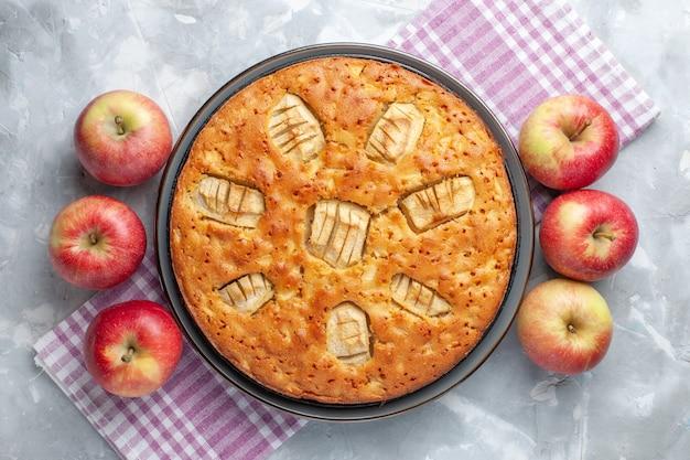 Vue de dessus délicieuse tarte aux pommes sucrée cuite au four avec des pommes sur le bureau blanc