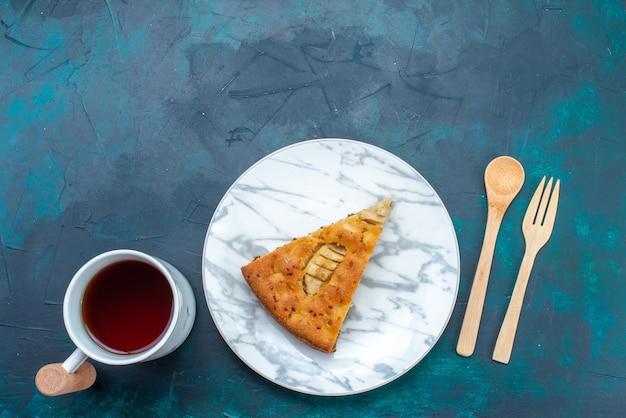 Vue de dessus délicieuse tarte aux pommes en tranches à l'intérieur de la plaque avec du thé sur fond bleu foncé gâteau aux fruits tarte au sucre sucré