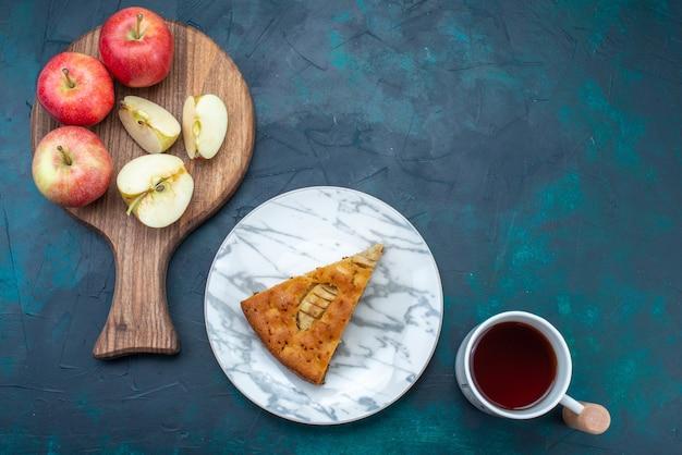 Vue de dessus délicieuse tarte aux pommes en tranches à l'intérieur de la plaque avec du thé et des pommes sur fond bleu foncé gâteau aux fruits tarte au sucre sucré