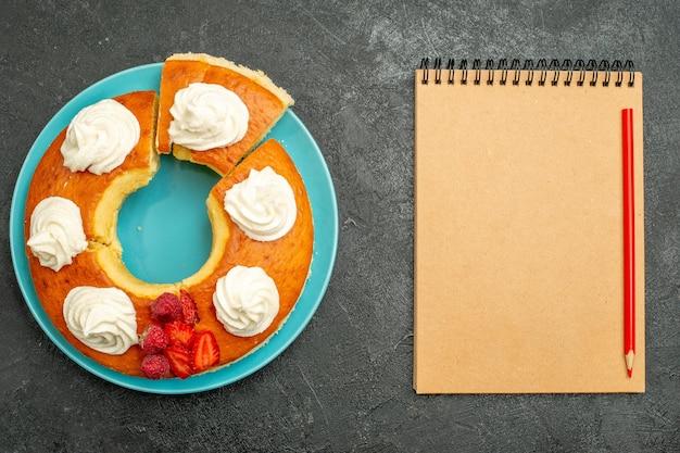 Vue de dessus d'une délicieuse tarte à la crème avec bloc-notes sur noir