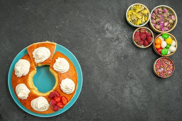Vue de dessus d'une délicieuse tarte à la crème avec des fleurs et des bonbons sur fond noir