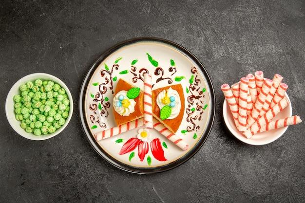 Vue de dessus délicieuse tarte à la crème à l'intérieur d'une assiette conçue avec des bonbons sur fond sombre gâteau tarte à la crème biscuit sucré