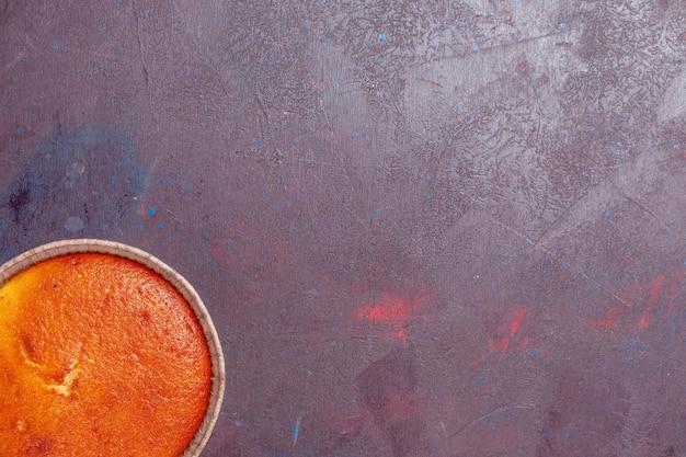 Vue de dessus délicieuse tarte ronde douce cuire au four sur fond sombre biscuit tarte sucrée pâte à gâteau au thé