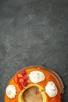 Vue de dessus délicieuse tarte ronde tranchée avec de la crème blanche sur fond gris tarte aux biscuits aux biscuits au thé sucrée