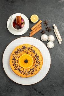 Vue de dessus délicieuse tarte sucrée à l'orange et tasse de thé sur la surface grise tarte sucrée gâteau dessert biscuit thé