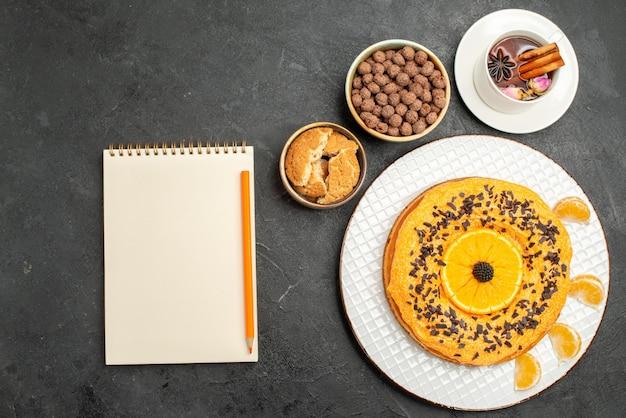 Vue de dessus délicieuse tarte sucrée avec une tasse de thé sur une surface gris foncé tarte aux biscuits biscuit dessert gâteau au thé