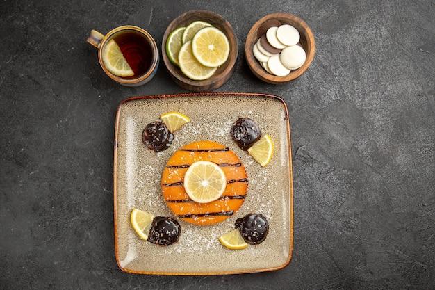 Vue de dessus délicieuse tarte sucrée avec des tranches de citron et une tasse de thé sur le fond gris gâteau tarte biscuit biscuit sucré
