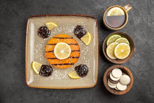 Vue de dessus délicieuse tarte sucrée avec des tranches de citron et une tasse de thé sur le fond gris gâteau tarte biscuit biscuits sucrés
