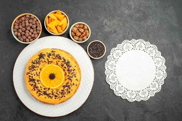 Vue de dessus délicieuse tarte sucrée avec des tranches d'orange sur la surface grise biscuit dessert tarte sucrée gâteau thé