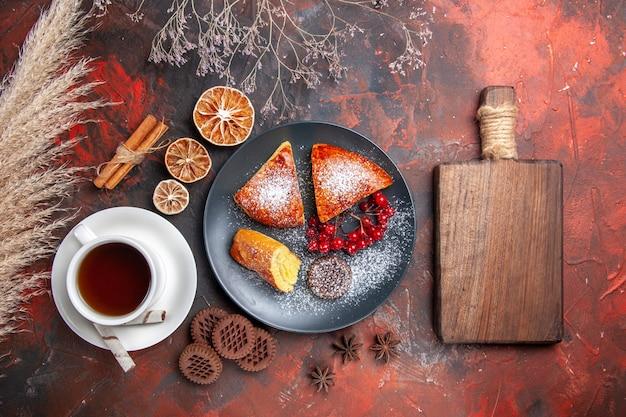 Vue de dessus délicieuse tarte en tranches avec une tasse de thé sur un gâteau au sol sombre