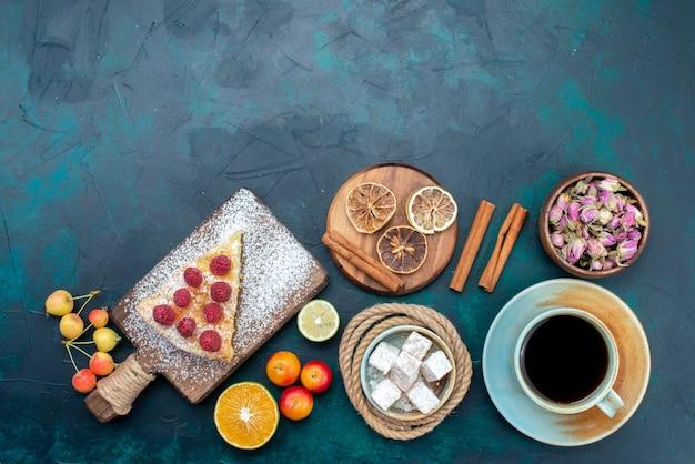 Vue de dessus délicieuse tranche de gâteau avec du thé à la cannelle et des fruits sur le bureau bleu foncé tarte gâteau sucré biscuit sucre