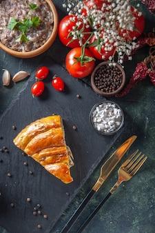 Vue de dessus de la délicieuse tranche de tarte à la viande avec des tomates rouges et de la viande farcie sur une surface sombre