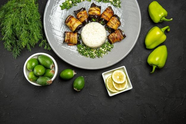 Vue de dessus de délicieuses aubergines cuites avec du riz sur la surface sombre dîner alimentaire huile de cuisson repas de riz