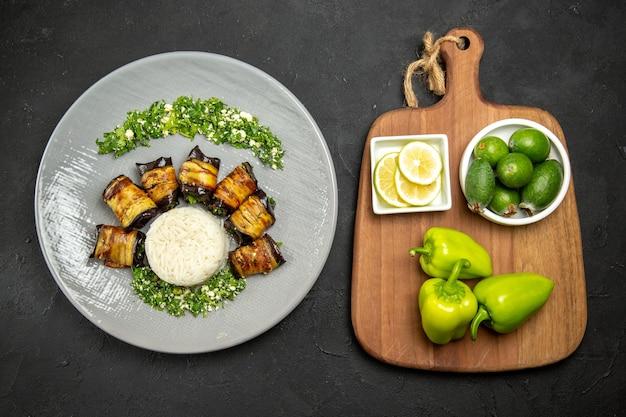 Vue de dessus de délicieuses aubergines cuites avec du riz sur une surface sombre pour le dîner, cuisson des repas de riz
