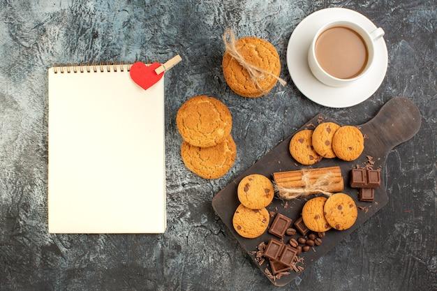 Vue de dessus de délicieuses barres de chocolat aux biscuits et d'une tasse de cahier à spirale de café sur une surface sombre et glacée