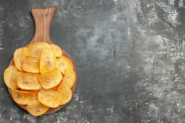 Vue de dessus de délicieuses chips maison sur une planche à découper en bois sur fond gris