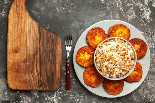 Vue de dessus de délicieuses côtelettes frites avec du riz cuit sur un plat de viande de rissole à surface sombre