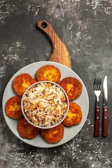 Vue de dessus de délicieuses côtelettes frites avec du riz cuit sur la rissole de viande de plat de surface sombre