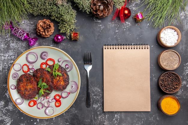 Vue de dessus de délicieuses côtelettes avec des rondelles d'oignon sur le plat de fond gris cuisine repas de viande