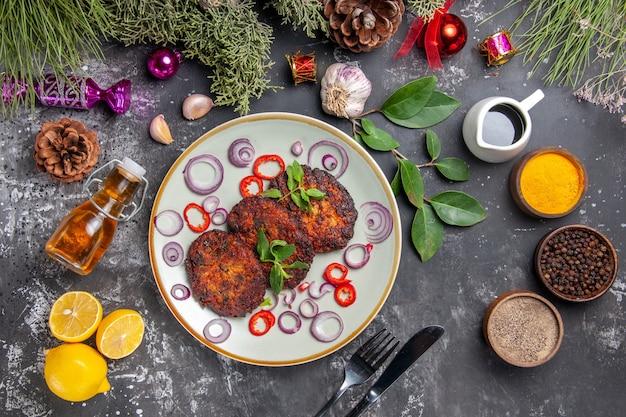 Vue de dessus de délicieuses côtelettes avec des rondelles d'oignon sur le plat de viande de fond gris repas