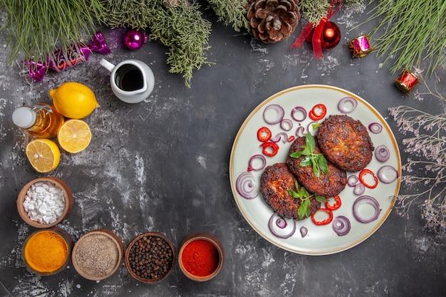 Vue de dessus de délicieuses côtelettes de viande avec assaisonnements sur le plat de photo repas fond gris clair