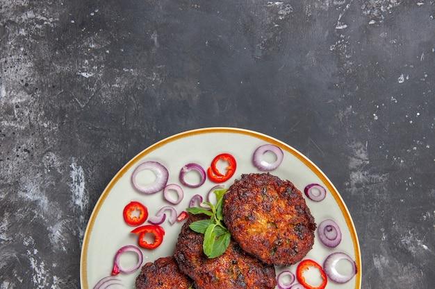 Vue de dessus de délicieuses côtelettes de viande avec des rondelles d'oignon