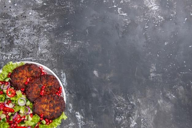 Vue de dessus de délicieuses côtelettes de viande avec salade fraîche