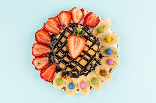Vue de dessus de délicieuses crêpes au chocolat avec des fraises rouges en tranches et des bananes à l'intérieur de la plaque sur le sol bleu glacier