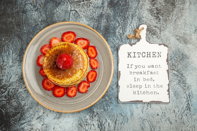 Vue de dessus de délicieuses crêpes au miel et aux fraises à la lumière