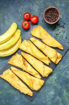 Vue de dessus de délicieuses crêpes aux bananes sur fond sombre pâte à gâteau couleur hotcake repas pâtisserie tarte viande