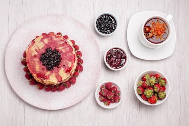 Vue de dessus de délicieuses crêpes aux fraises tasse de thé sur un bureau blanc tarte biscuit gâteau aux fruits baies sucrées