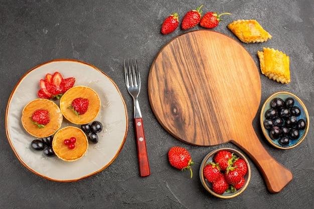 Vue de dessus de délicieuses crêpes aux fruits sur la tarte aux fruits gâteau de surface sombre