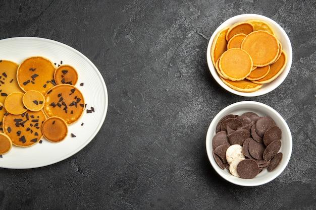 Vue de dessus de délicieuses crêpes avec chips de chocolat et biscuits sur fond sombre