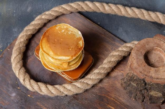 Vue de dessus de délicieuses crêpes avec des cordes sur le petit-déjeuner repas sucré fond gris