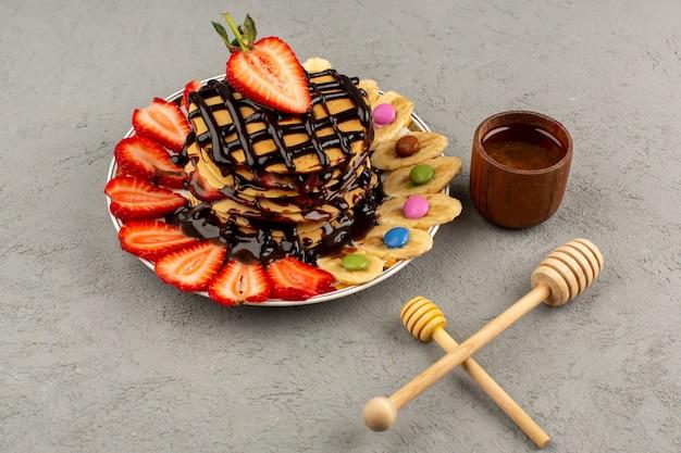 Vue de dessus de délicieuses crêpes avec des fraises en tranches de chocolat rouge et des bananes en tranches à l'intérieur de la plaque blanche sur le sol clair